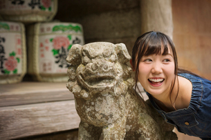 Young woman wearing blue dress standing next to stone sculpture of lion at Shinto Sakurai Shrine, Fuの写真素材 [FYI02262043]