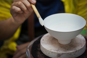Close up of person working in a Japanese porcelain workshop, glazing white bowls with paintbrush.の写真素材 [FYI02262046]