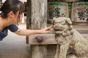 Young woman wearing blue dress touching stone sculpture of lion at Shinto Sakurai Shrine, Fukuoka, Jの写真素材 [FYI02262049]