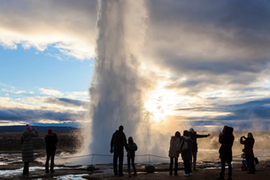Silhouette of group of people standing around fountain of geyser at twilight.の写真素材 [FYI02262055]