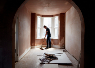 A builder sweeping and tidying up in a renovated replastered house with an archway.の写真素材 [FYI02262057]