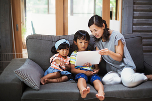 Woman, boy and young girl sitting on a grey sofa, looking at digital tablet.の写真素材 [FYI02262059]