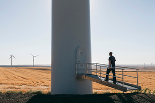 A wind farm technician standing and using a laptop at the base of a turbine on a wind farm in open cの写真素材 [FYI02262061]