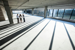 Mixed race team of business people touring a new empty raw office space.の写真素材 [FYI02262062]