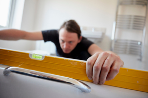 A builder using a spirit level to check his work, refurbushing a bathroom.の写真素材 [FYI02262064]