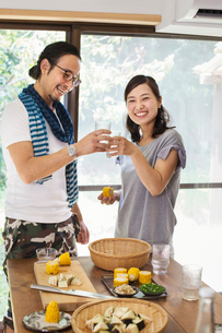 Smiling man and woman standing indoors by a table set with food, holding drinking glasses, toasting.の写真素材 [FYI02262072]