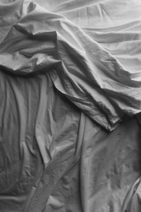 Black and white close up of wrinkled cotton sheets on bed.の写真素材 [FYI02262078]