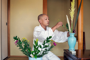 Buddhist monk with shaved head wearing white robe kneeling on floor, arranging flowers in blue vase.の写真素材 [FYI02262088]