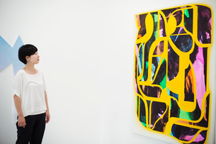 Woman with short black hair wearing white shirt standing in art gallery, looking at modern painting.の写真素材 [FYI02262100]