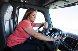 Caucasian woman driver parked and using the GPS mapping device in the cab of a  commercial truck.の写真素材 [FYI02262111]