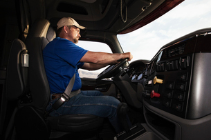 Caucasian man driver in the cab of a  commercial truck.の写真素材 [FYI02262123]