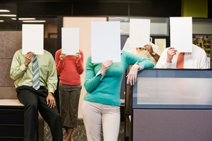 Team of business people standing with blank pieces of paper in front of their faces.の写真素材 [FYI02262147]