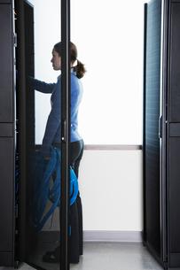 Caucasian woman lab technician next to racks in a computer server farmの写真素材 [FYI02262152]