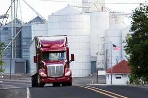 A red commercial truck driving past grain elevators in the farm country of eastern Washington, USA.の写真素材 [FYI02262182]