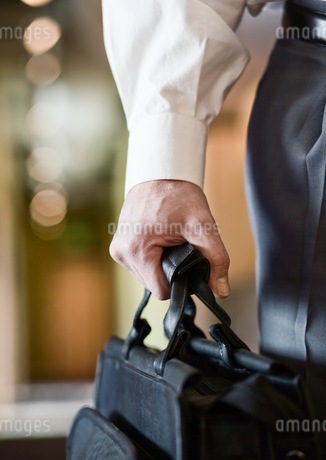 A closeup of the hand of a businessman holding a brief case.の写真素材 [FYI02262187]
