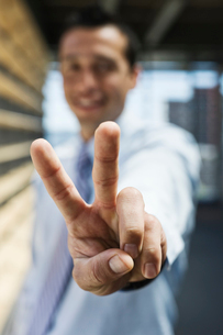 Businessman gesturing a victory sign to the camera.の写真素材 [FYI02262200]