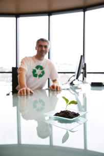 A Caucasian businessman wearing a recycle t shirt  while sitting at his office desk in front of a laの写真素材 [FYI02262207]