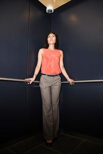 Asian businesswoman standing in the corner of an elevator in a large office building.の写真素材 [FYI02262209]
