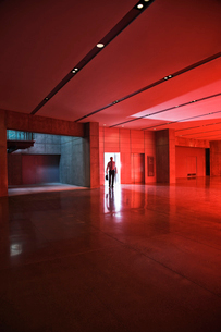 Businessman walks through the door of a lobby area that is lit by daylight through red tinted glass.の写真素材 [FYI02262211]