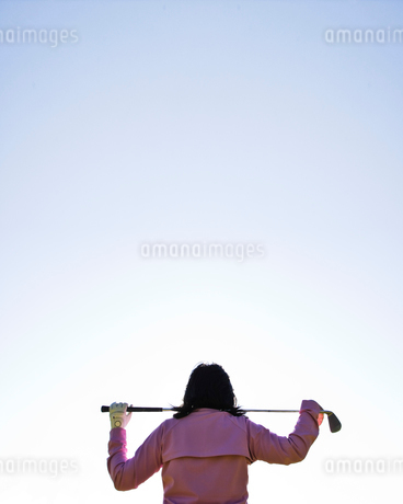 A woman golfer holding a club over her shoulders.の写真素材 [FYI02262212]