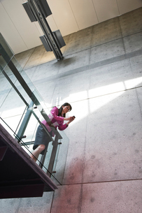 Businesswoman texting from a stairway balcony in large office building.の写真素材 [FYI02262213]