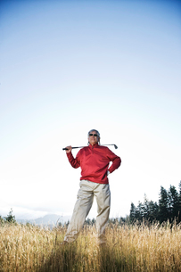 Senior golfer standing in heavy rough pondering his next shot.の写真素材 [FYI02262221]