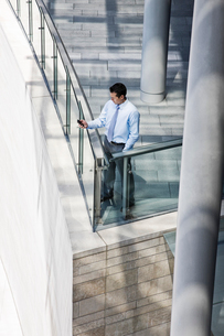 Caucasian businessman texting from a balcony on a large office buildingの写真素材 [FYI02262223]
