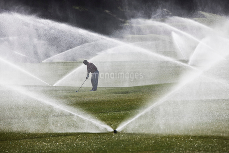 A golfer hitting his second shot on the fairway when the sprinkler system turns on.の写真素材 [FYI02262228]