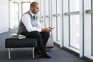 Hispanic businessman texting while sitting on a bench in a business office lobby.の写真素材 [FYI02262229]