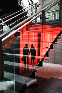 Two businesspeople silhouetted in reflections on the glass around a stairwell of a large office builの写真素材 [FYI02262230]