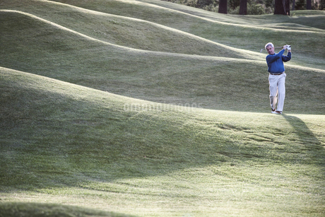 Senior golfer hitting a second shot from the fairway of a golf course.の写真素材 [FYI02262231]