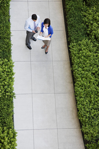 View from above of a businessman and woman looking at paperwork while standing on a sidewalk.の写真素材 [FYI02262237]