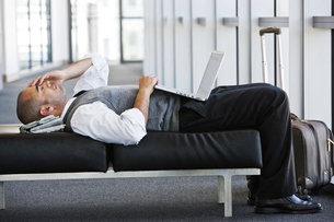 Exhausted businessman taking a short break laying on a bench in an office lobby.の写真素材 [FYI02262238]