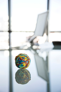 A rubber band ball sitting on a reflective desk in an office.の写真素材 [FYI02262251]