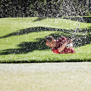 Senior golfer playing out of a bunker on the golf course.の写真素材 [FYI02262256]