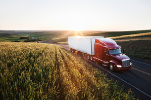 commercial truck driving though wheat fields of eastern Washington, USA at sunset.の写真素材 [FYI02262257]