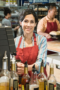 Hispanic woman at the cash register of a bakery/coffee shop.の写真素材 [FYI02262277]