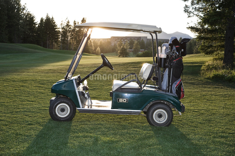 A golf cart with bags sitting on a golf course.の写真素材 [FYI02262288]