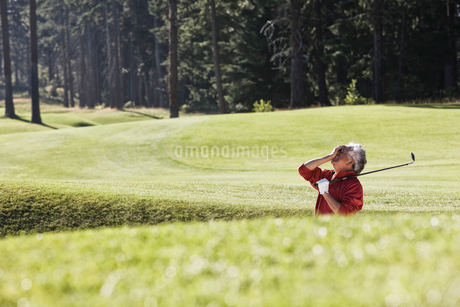 Golfer reacting with frustration at a missed shot from a bunker near the green on a golf course.の写真素材 [FYI02262324]