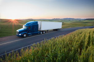 Commercial truck driving though wheat fields of eastern Washington, USA at sunset.の写真素材 [FYI02262325]