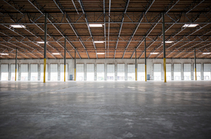 Wide angle interior view of large empty warehouse and loading dock doorsの写真素材 [FYI02262327]