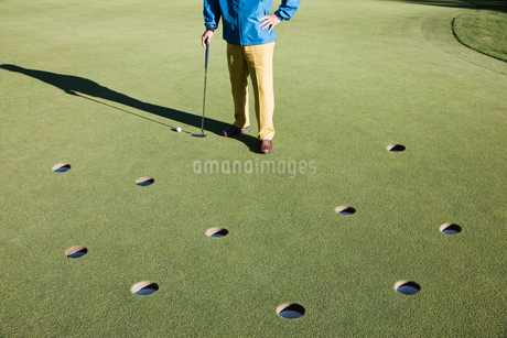 A golfer with way too many choices in possible putts on the green of a golf course.の写真素材 [FYI02262329]