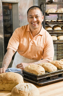 Hispanic man baker and some of the loaves of bread he baked this morning.の写真素材 [FYI02262332]