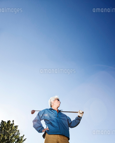A young Asian senior man ready to hit his next golf shot on a golf course.の写真素材 [FYI02262333]