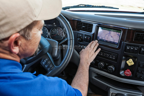 Driver parked by the side of the road using a GPS mapping device in the cab of a  commercial truck.の写真素材 [FYI02262341]