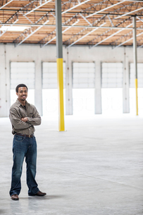 Black man owner of a new warehouse standing inside in front of loading dock doors.の写真素材 [FYI02262344]