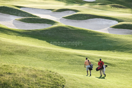 View from above of two golfers walking on a fairway toward the green of a golf course.の写真素材 [FYI02262348]