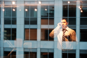 Reflection in windows of a businessman working late at nightの写真素材 [FYI02262356]