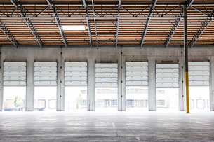 Wide angle interior view of large empty warehouse and loading dock doorsの写真素材 [FYI02262378]