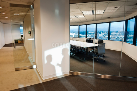 Shadows of two business people on the wall outside of a company conference room..の写真素材 [FYI02262385]